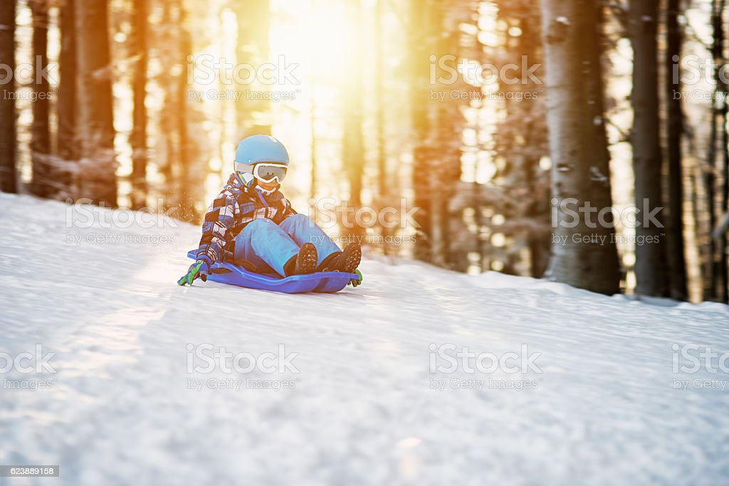 Little boy speeding on his sled in winter forest stock photo