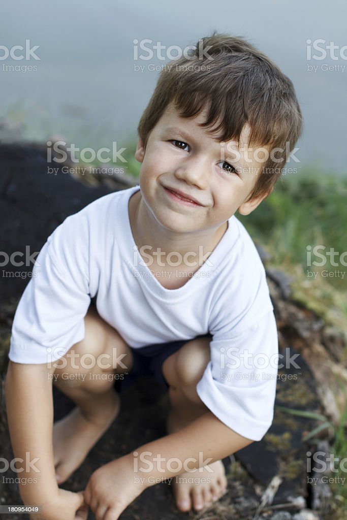 Little boy squat at riverside royalty-free stock photo