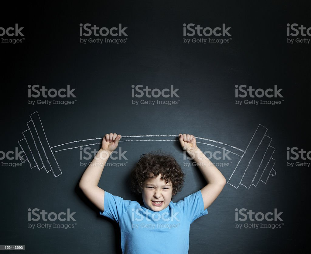 A little boy standing against a blackboard stock photo