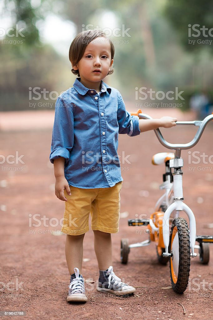 Little boy standing and holding bike stock photo