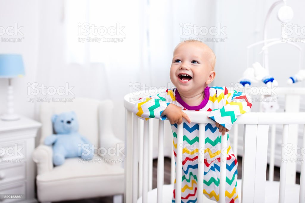 Little boy standing in bed stock photo