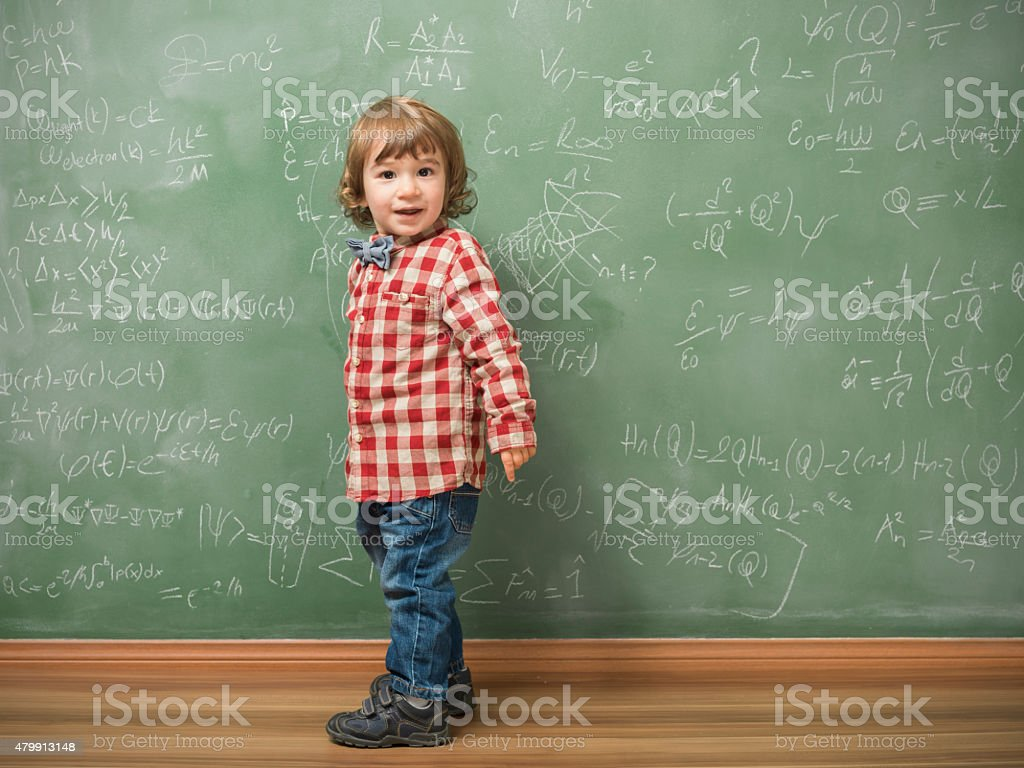Little boy standing in front of green blackboard stock photo