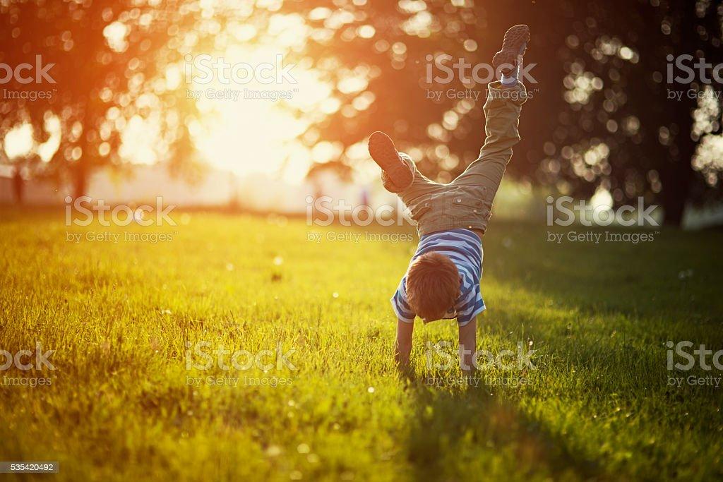 Little boy standing on hands on grass stock photo