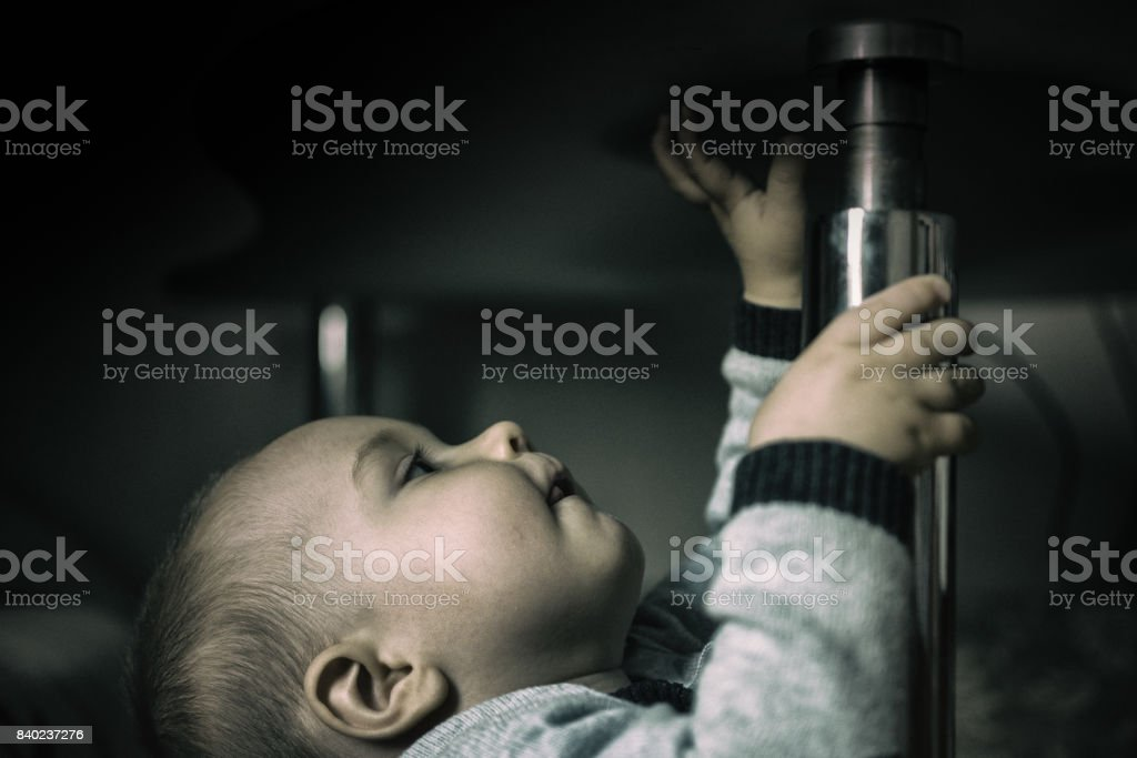 little boy stands and holds onto the table to not fall and extends up stock photo