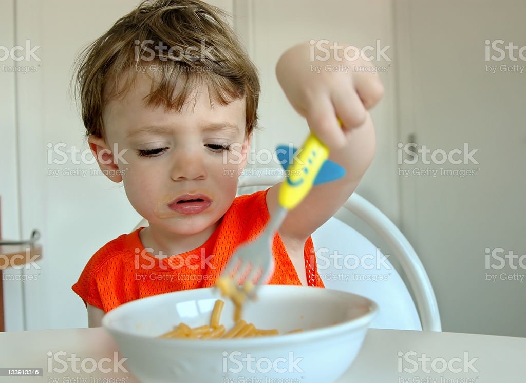 Little boy sticking airplane fork into bowl of pasta stock photo