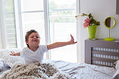 Little boy stretching on bed in the morning.
