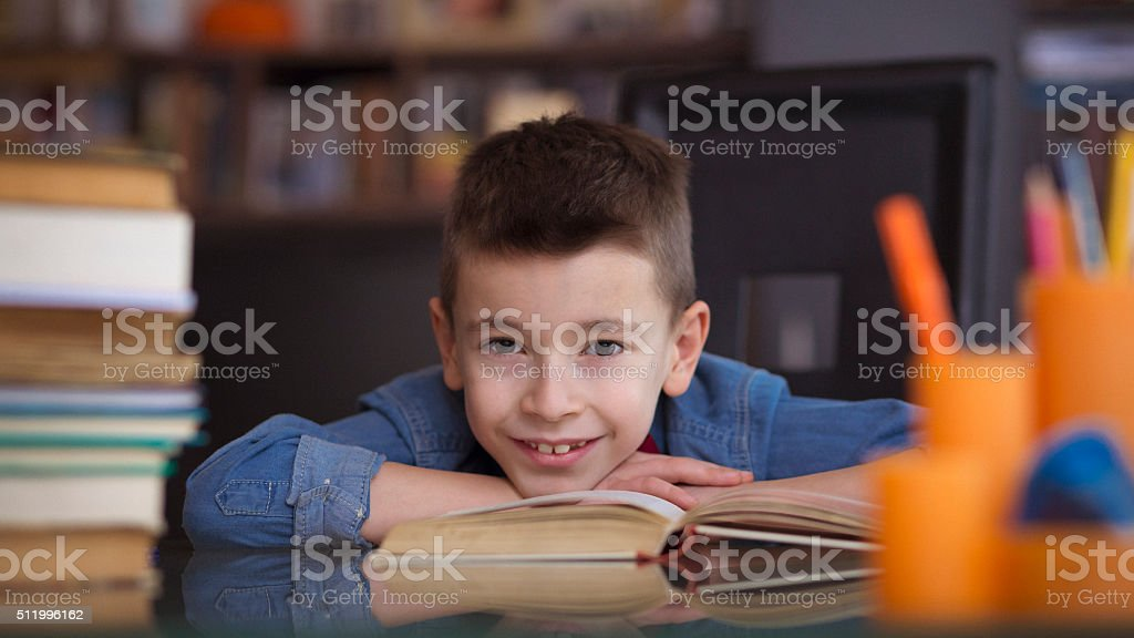 Little boy studying and smiling for the camera stock photo