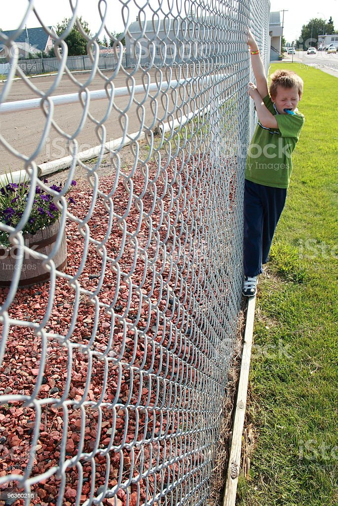little boy sucking on candy holds onto chain link fence royalty-free stock photo