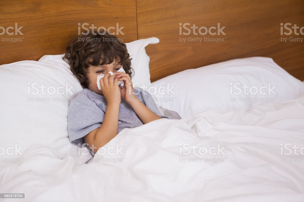 Little boy suffering from cold as he lies in bed stock photo