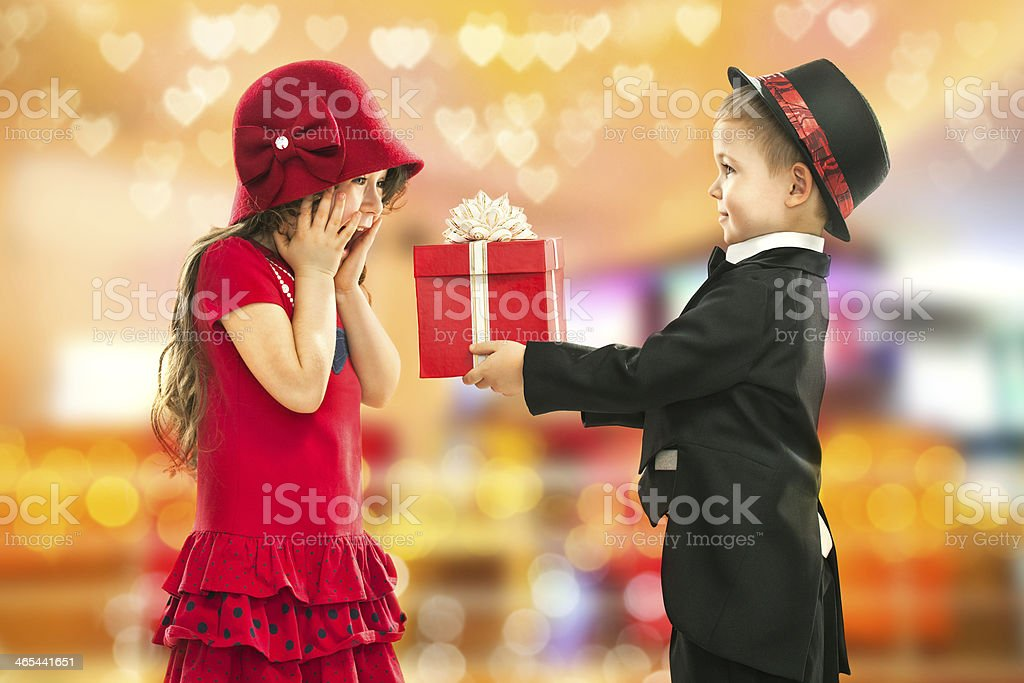 Little boy surprising an excited girl with a gift stock photo