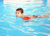 Little Boy Swimming in Pool with Arm Floats