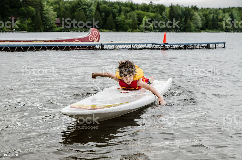 Little boy swimming on surf board stock photo