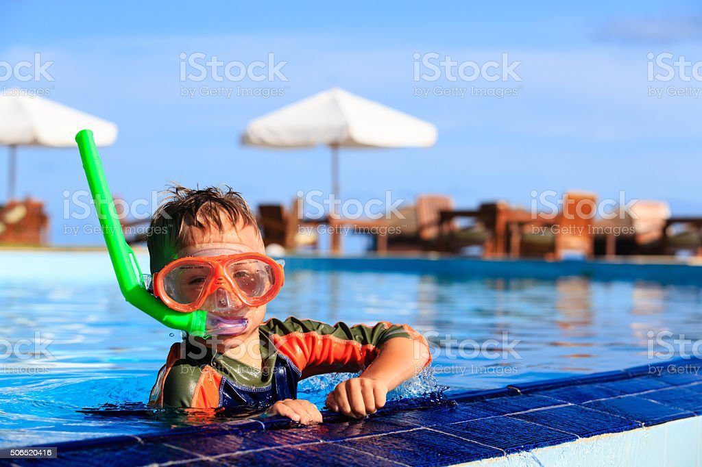 little boy swimming with mask in pool stock photo