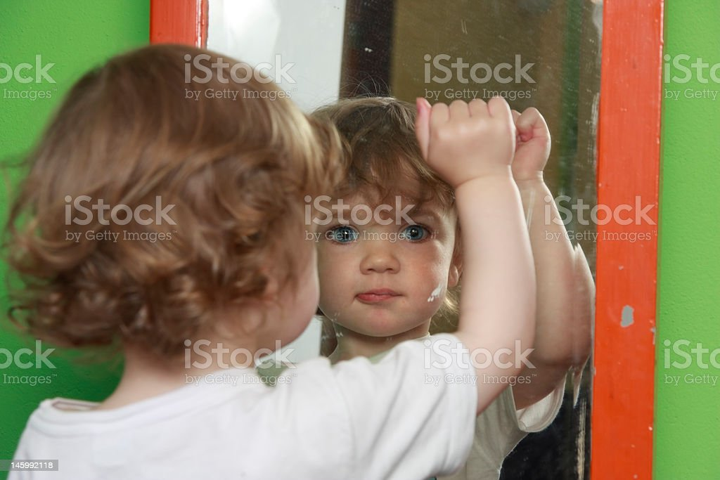 A little boy taking a look at the mirror  royalty-free stock photo