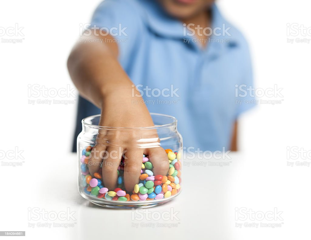 Little boy taking candy from jar stock photo