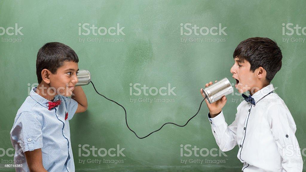 Little boy talking on tin can phone before blackboard stock photo