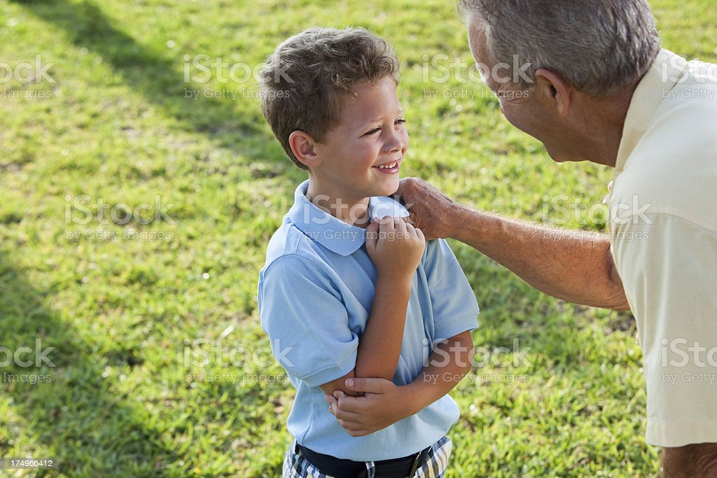 Little boy talking to grandfather stock photo