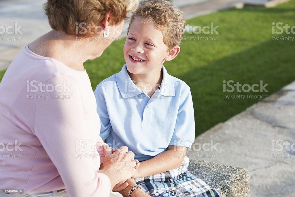 Little boy talking to grandmother stock photo