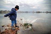 Little Boy Throwing Big Stone Into Lake