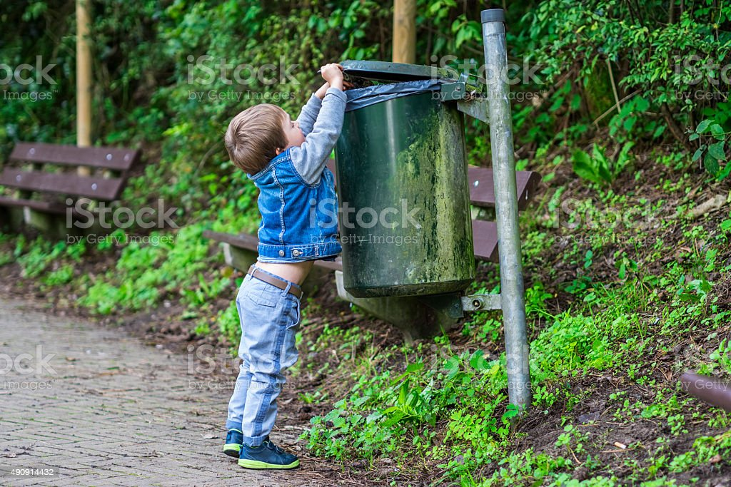 Little boy throwing trash in the bin stock photo