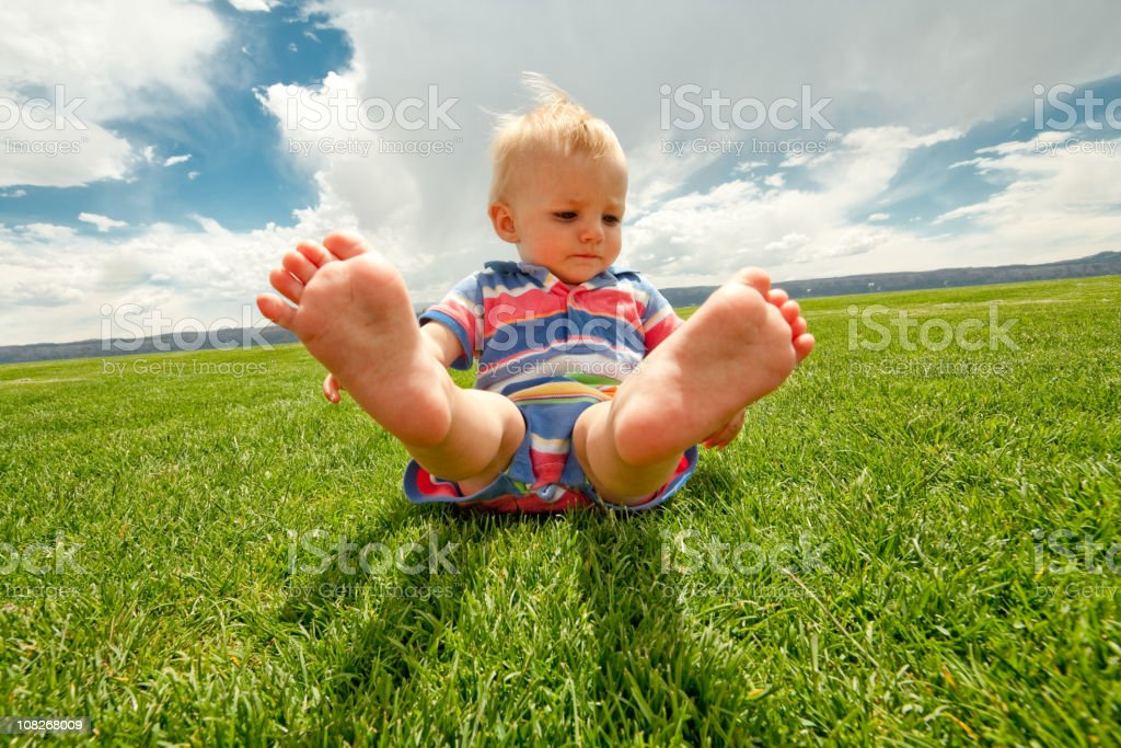 Little Boy Toddler on the Grass with feet up royalty-free stock photo