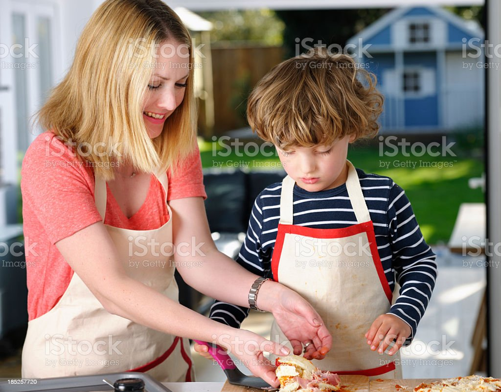 Little Boy/ Toddler Preparing Pizza With Their Mother royalty-free stock photo