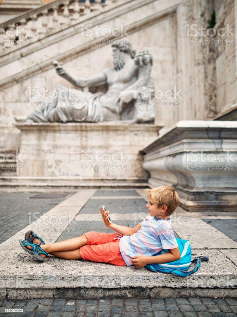 Little boy tourist resting in Piazza del Campidoglio, Rome, Italy stock photo