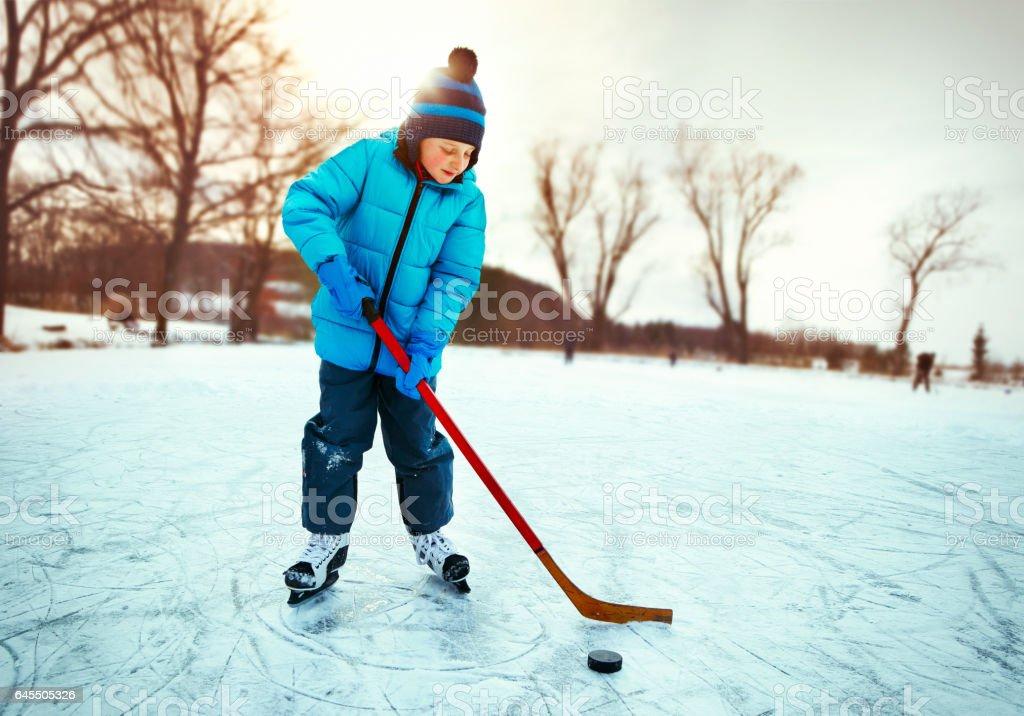Little boy training ice hockey on the pond