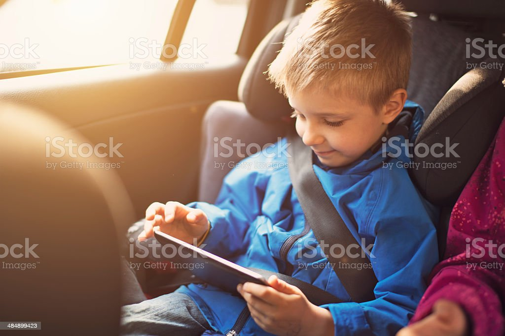 Little boy travelling in car with tablet stock photo