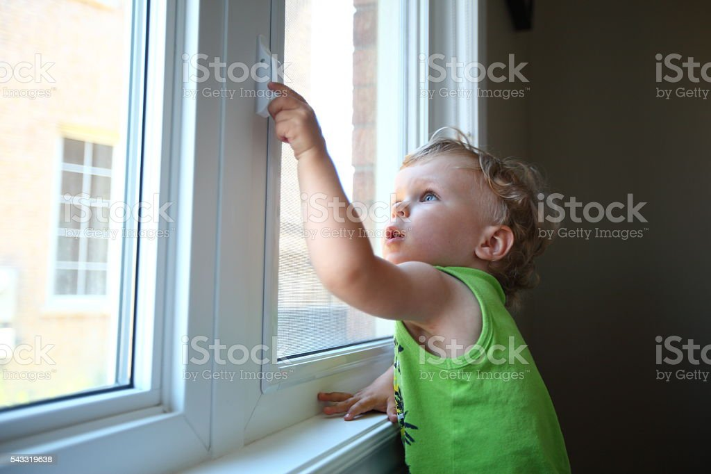 Little boy trying to open the window stock photo