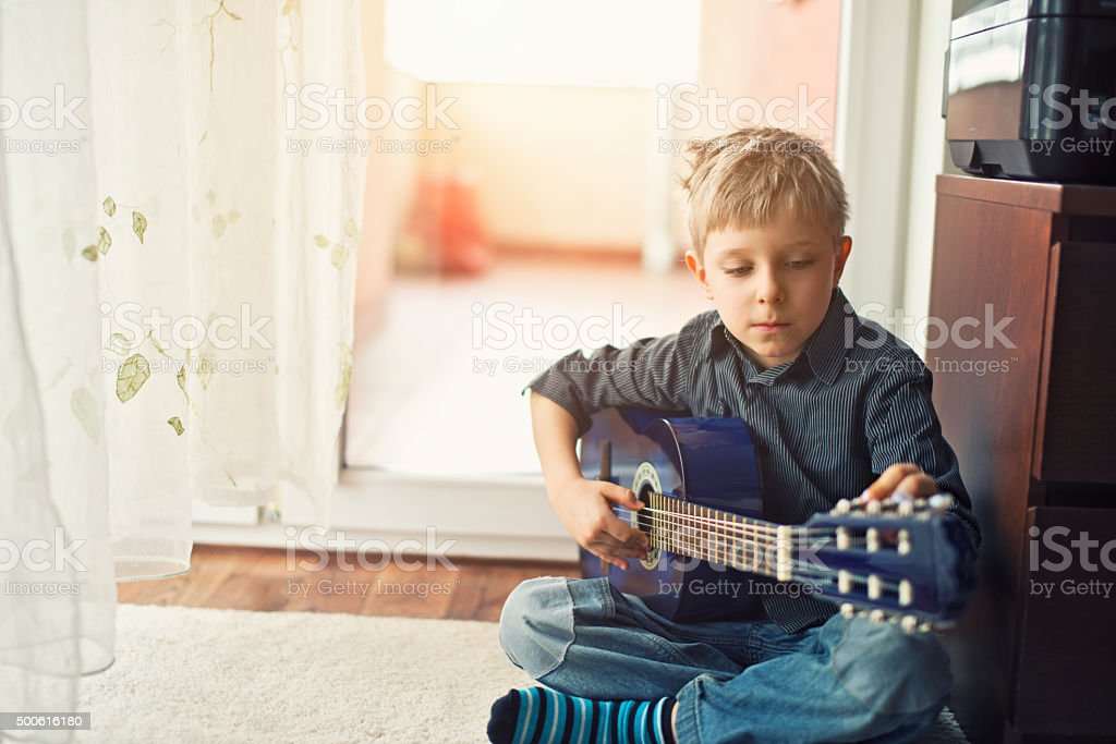 Little boy tuning his little blue acoustic guitar. stock photo