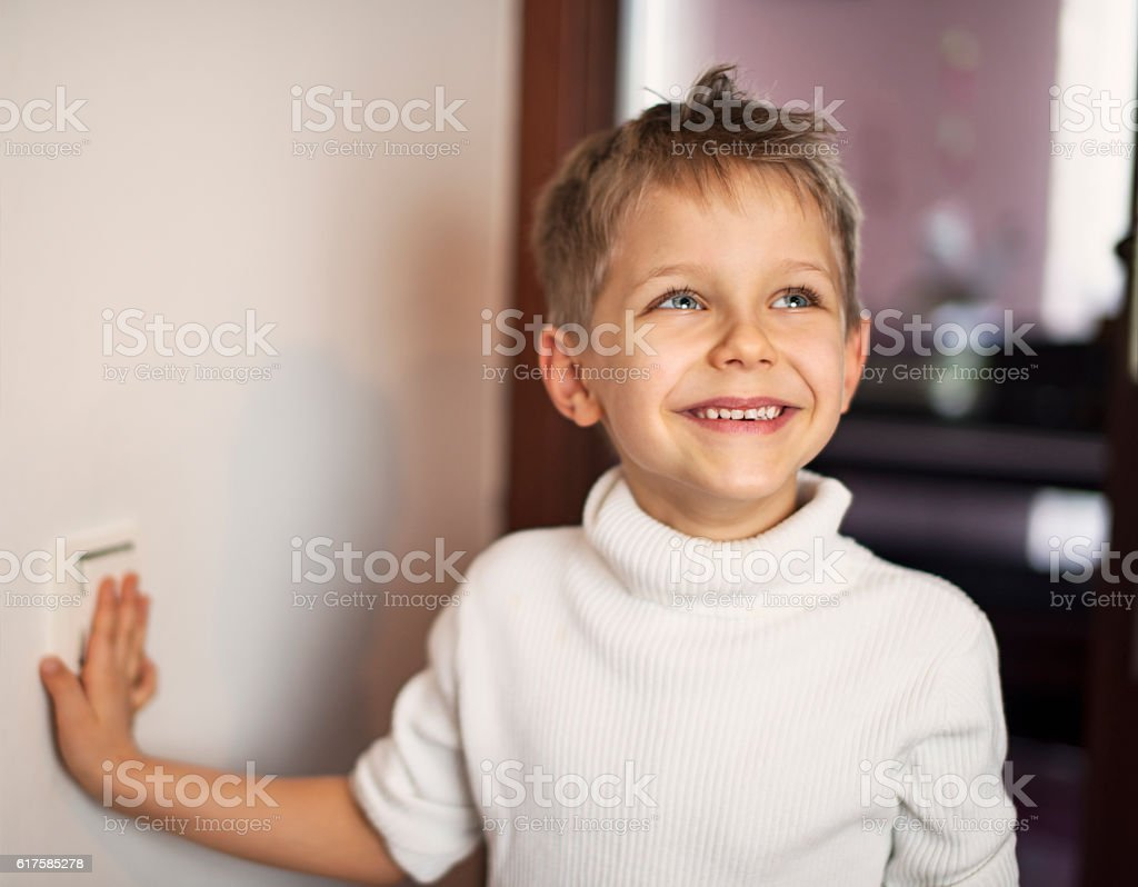 Little boy turning on light stock photo