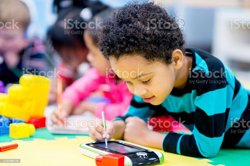Little Boy using a Tablet PC in Preschool stock photo