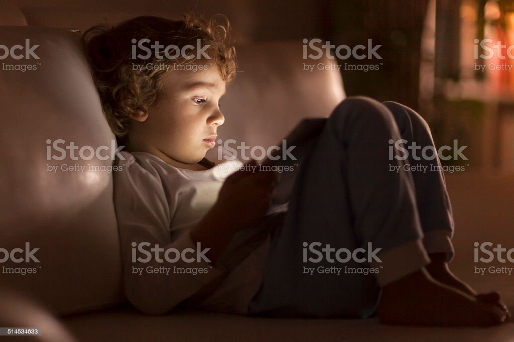 Little boy using digital tablet in bed stock photo