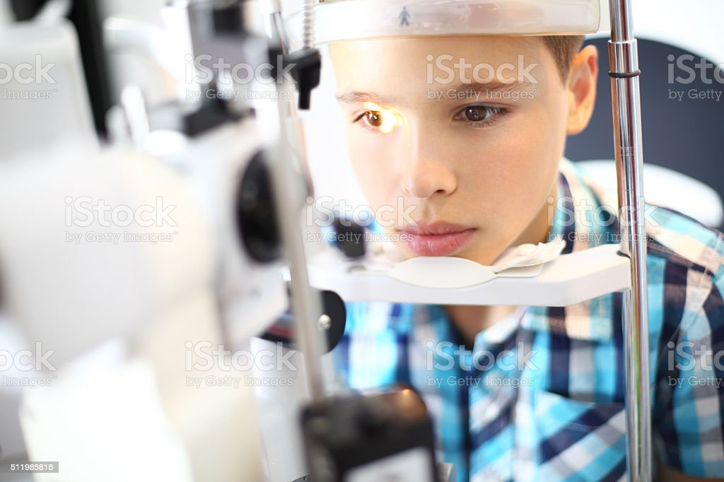 Little boy visiting optician. stock photo