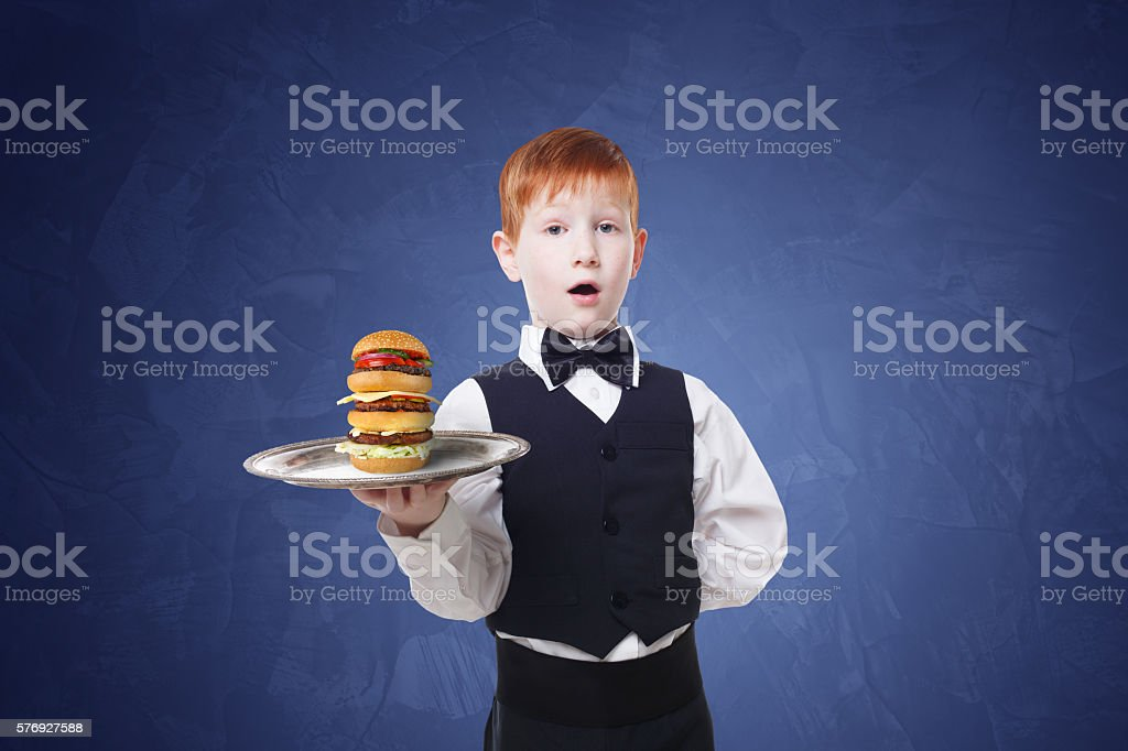 Little boy waiter stands with tray serving hamburger stock photo