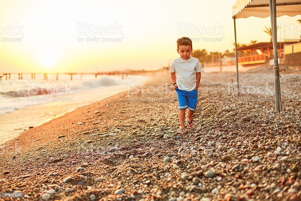 Little boy walking along sunny beach stock photo