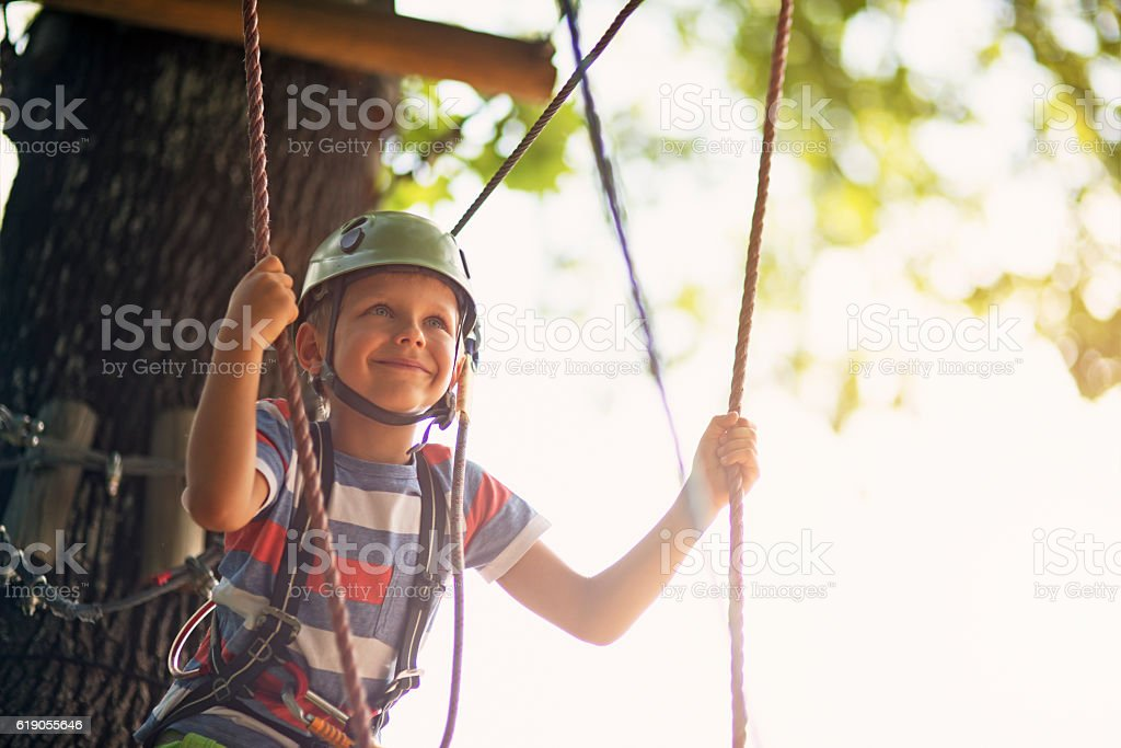 Little boy walking in outdoors ropes course stock photo