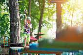 Little boy walking in outdoors ropes course