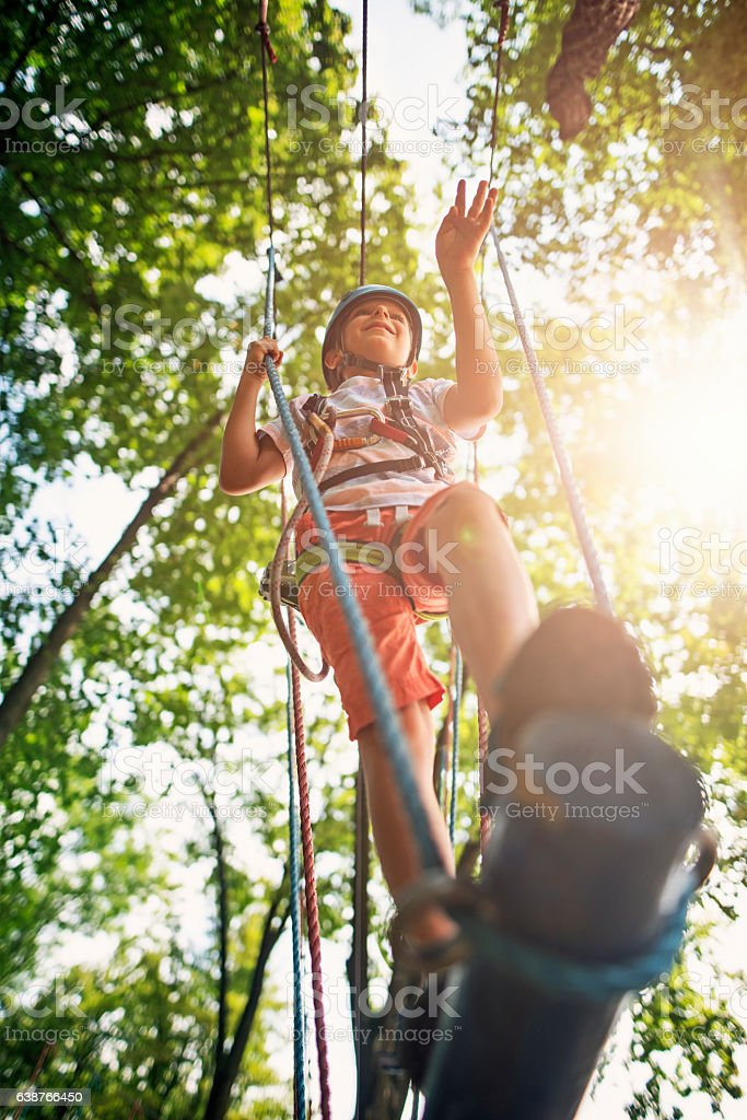 Little boy walking in ropes course in outdoors adventure park stock photo
