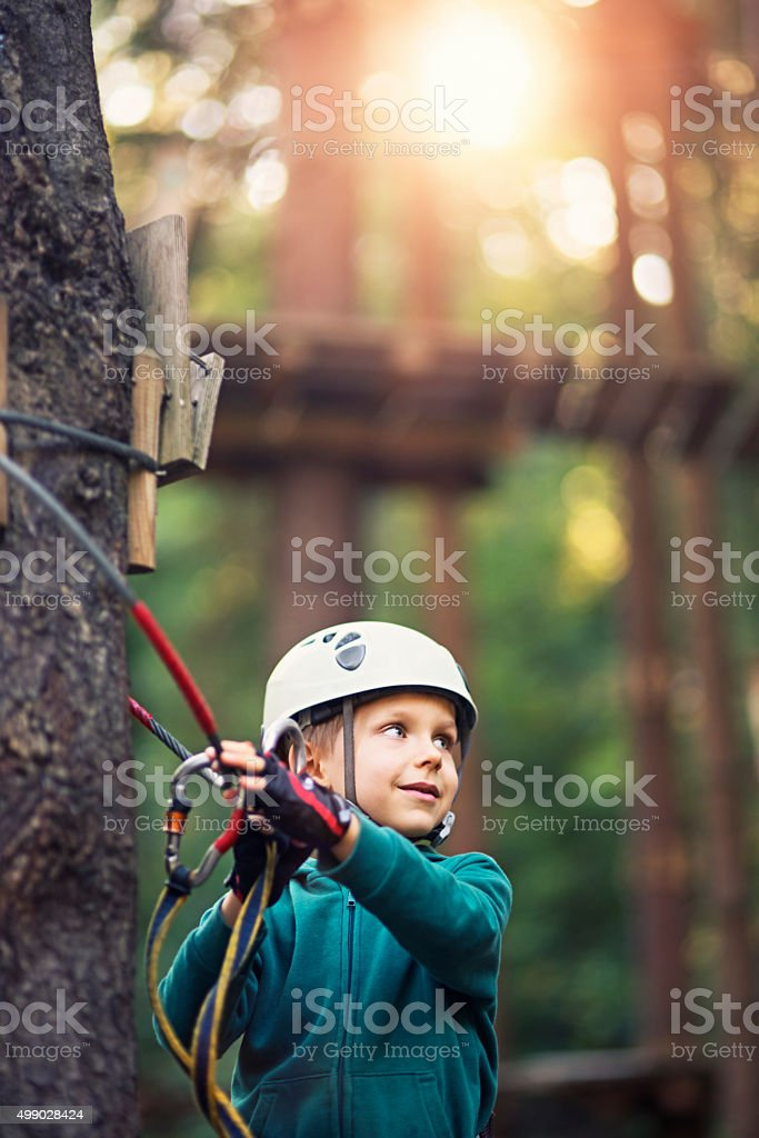 Little boy walking on ropes course in outdoors adventure park stock photo