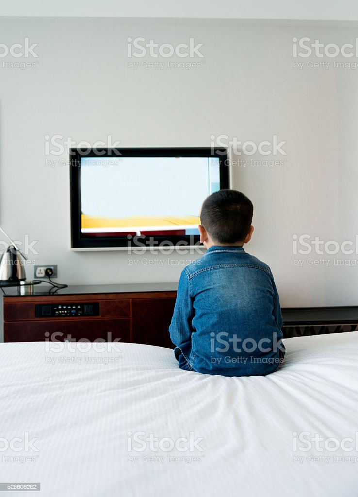 Little boy watching TV on bed stock photo