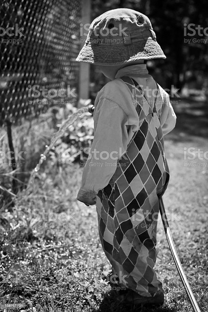 Little boy watering grass under the sun royalty-free stock photo