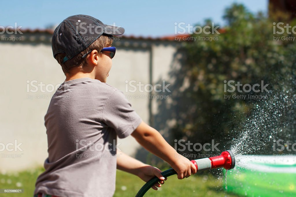 Little boy watering with hose royalty-free stock photo