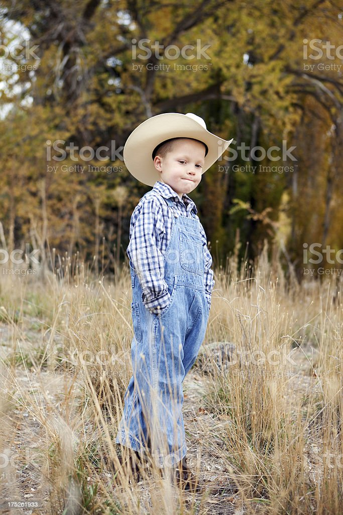 Little Boy Wearing Denim Overalls and Cowboy Hat royalty-free stock photo