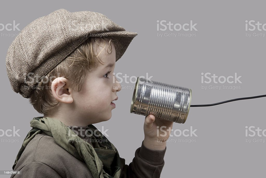 Little Boy Wearing Newsboy Cap Talking On Tin Can Phone royalty-free stock photo