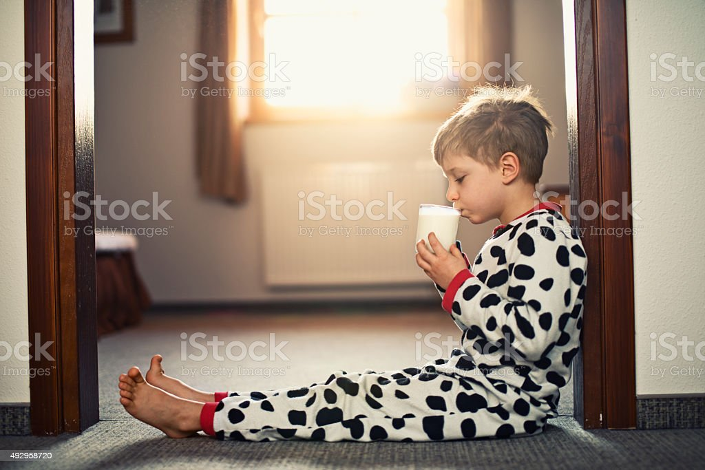 Little boy wearing pyjamas drinking glass of milk in morning stock photo