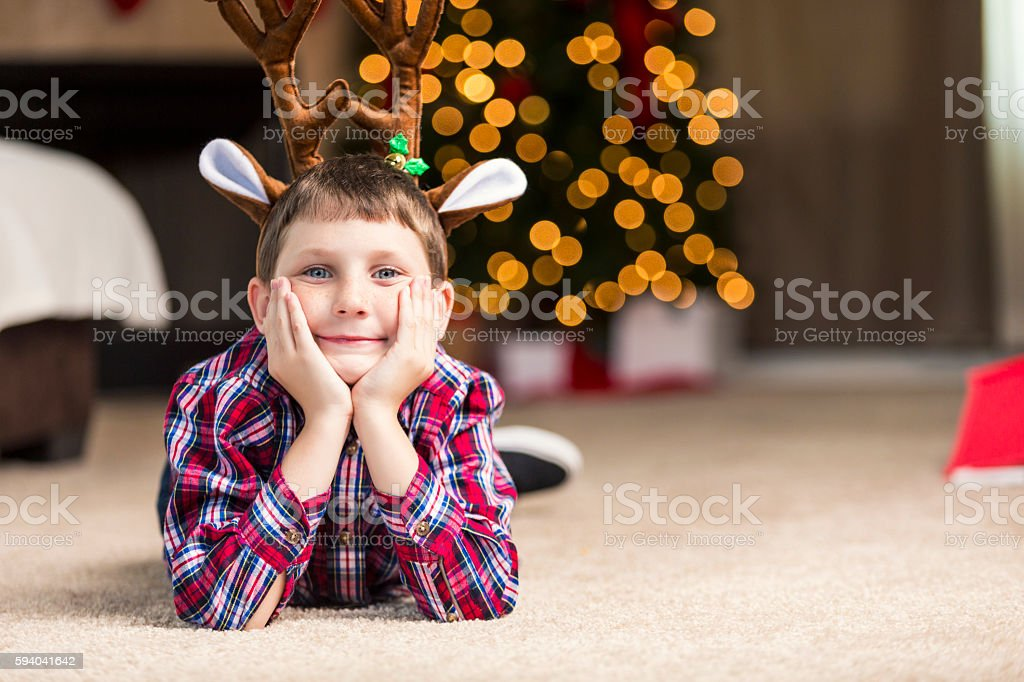 Little boy wearing reindeer antlers anxiously waits for Christmas morning stock photo