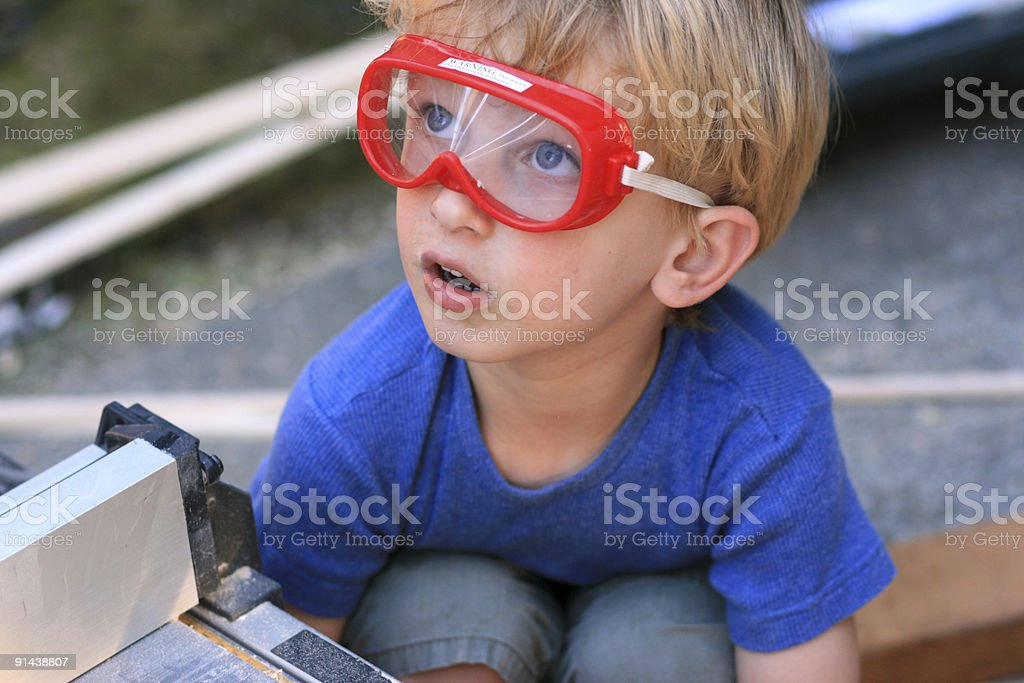 Little boy wearing safety goggles surrounded by DIY material royalty-free stock photo