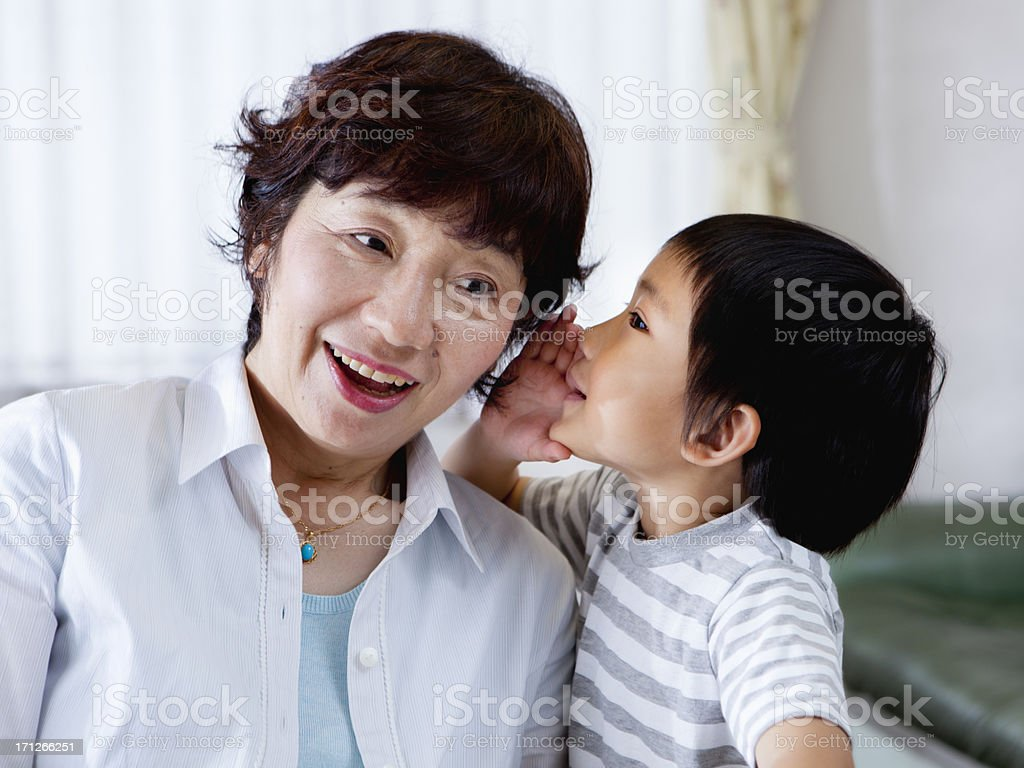 Little boy whispering to grandmother's ear royalty-free stock photo